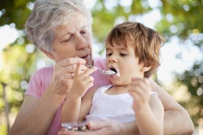 Бабушка кормит внука - переедание